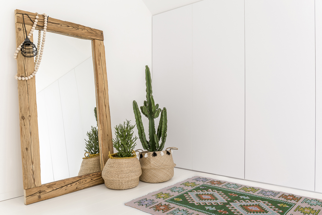 White room with mirror with wooden frame and decorative cactus and our vintage kilim rug